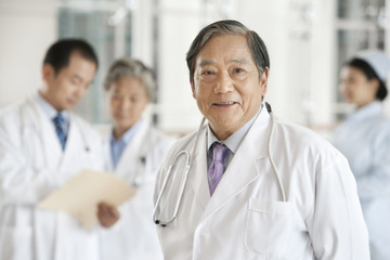 Senior Doctor with Doctors and Nurse in Background