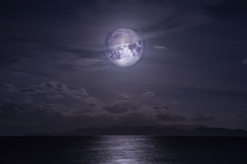 Full moon over the sea. Elements of this image furnished by NASA