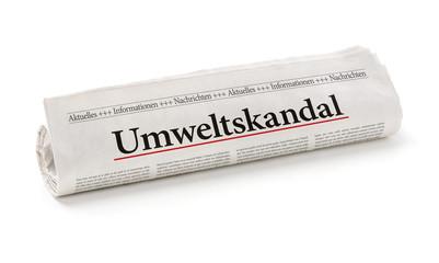 Zeitungsrolle mit der Überschrift Umweltskandal