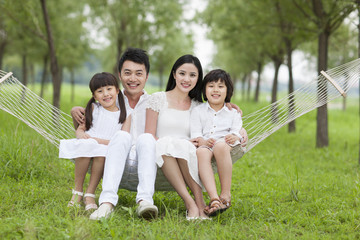 Happy young family sitting in a hammock outdoors