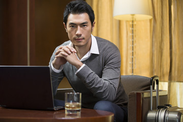 Portrait of young businessman in hotel room