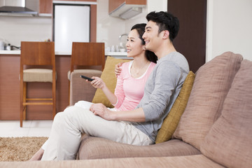 Cheerful young couple watching TV in living room