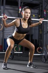 Young woman lifting barbell at gym
