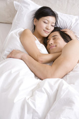 Asian couple cuddling on bed