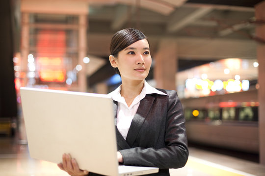 Young businesswoman using her laptop at the train station