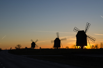 Windmills silhouettes by roadside at sunset on the Swedish Island Oland