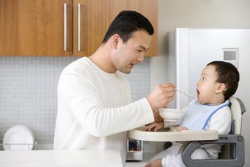 Man feeding infant