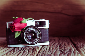 Vintage camera with roses on old wood background.