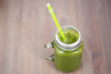 A green smoothie in a mason jar with tube