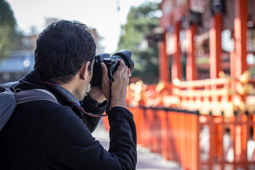 a man holding his camera taking photo of red Japanese temple or Fushimi Inari Shrine