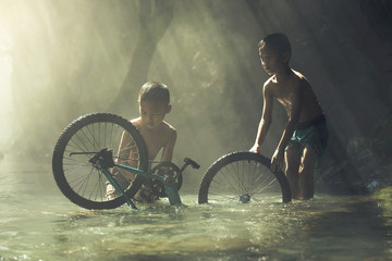 Child playing with bicycle in the creek