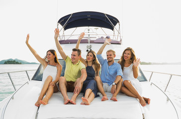 Tropic vacation. Group of young beautiful people smiling and showing hello by hands on the yacht