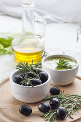 Marinated black olive and homemade sauce mayonnaise in ceramic pots. Marinated black olive and homemade sauce mayonnaise in ceramic pots with parsley, rosemary and olive oil on wooden board.