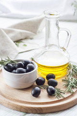 Bottle of olive oil and marinated black olives. Marinated black olives in ceramic bowl and wooden spoon with bottle of olive oil.