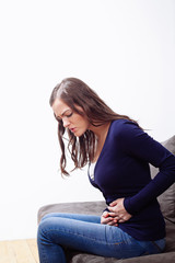 Young Woman Sitting On Sofa Suffering From stomach ache