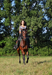 Pretty girl riding in the forest road in summer evening