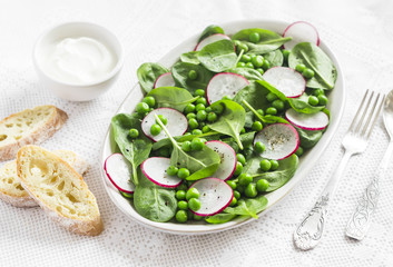 Green peas, radish and baby spinach salad on ceramic plate on a light background. Healthy and vegetarian food