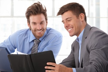 Happy businessman looking at personal organizer