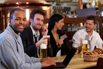 Happy office worker using laptop at bar