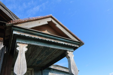 Wall Mural - Front porch of a very old wooden house in the remote Russian village in the summer against a blue sky