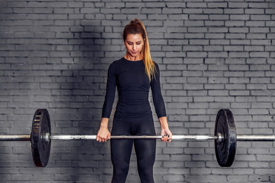 Woman with weight barbell doing deadlift exercise