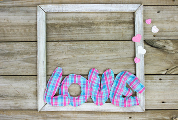 The word LOVE in pink and blue fabric on rustic wood frame with hearts