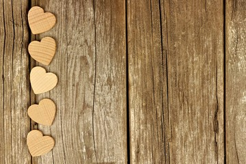 Valentines Day wooden hearts forming a side border on a rustic wood background