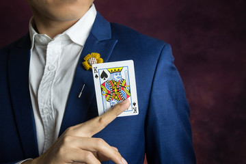 man in blue suit picking king spades