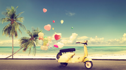 Wall Mural - Classic yellow motorcycle with heart balloon on beach blue sky concept of love in summer and wedding honeymoon - vintage color effect