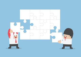 Businessman help each other to assemble blank jigsaw