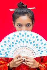 Asian woman with fan on red background