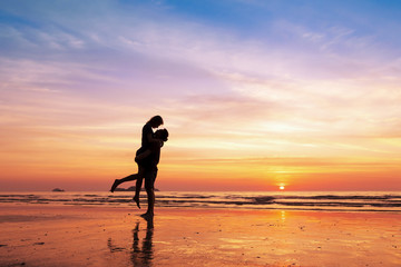 Couple kissing on the beach with beautiful sunset in background