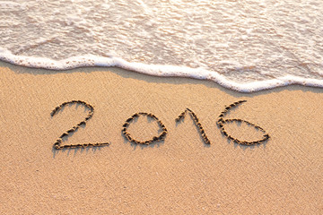 2016 written on a sandy beach for new year concept