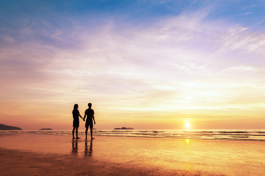 Two lovers standing together on a beach thinking about life