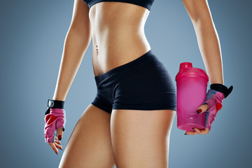 Attractive young woman with protein shake bottle