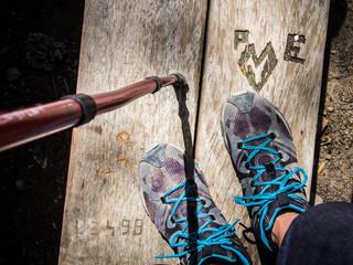 Ausicht auf Wanderschuhe und Wanderstock - stehend vor Schnitzerei
