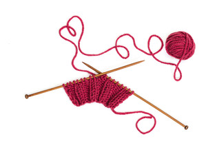 Knitting pattern on wooden needles of woolen threads red color