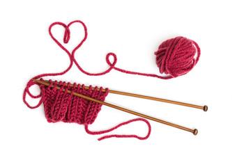 Knitting pattern on wooden needles of woolen threads