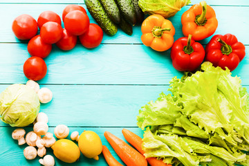 Frame of vegetables with copy space on blue wooden background. Top view