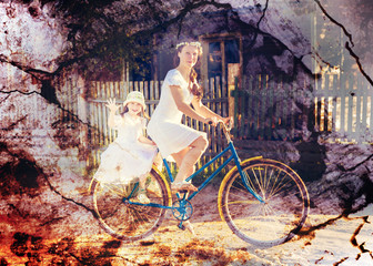 Mom and daughter on a bicycle.