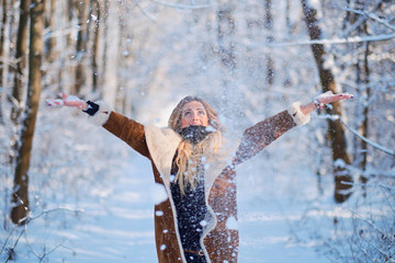 Blonde young woman standing in snowfall winter forest