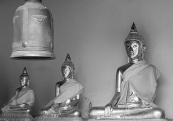 Monochrome photograph of Metallic Buddha image and bell