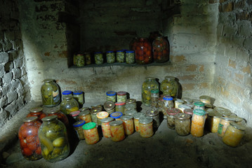 Preserved vegetables in glass jars staying in the cellar