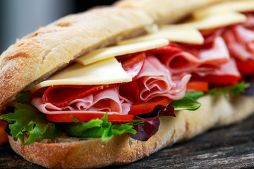 Photo on textile frame Snack Sandwich with lettuce, slices of fresh tomatoes, salami, hum and cheese.