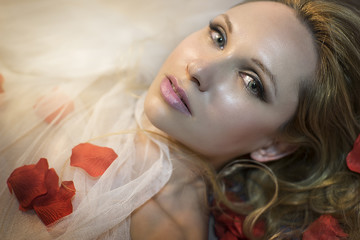 Pretty Sensual blonde with fine white silk cloth lying in bed