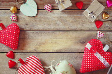 top view image of colorful heart shape chocolates, fabric hearts and gift boxes on wooden table. valentine's day celebration concept. retro filtered