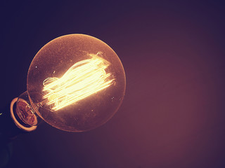 Beautiful retro light bulb is glowing. Vintage style photo and filtered process.