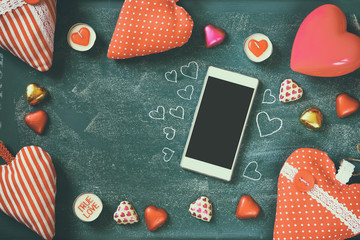 top view image of smartphone, colorful heart shape chocolates, fabric hearts on blackboard background. valentine's day celebration concept
