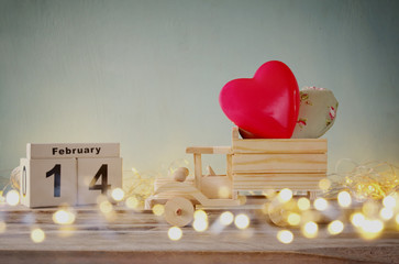 photo of February 14th wooden vintage calendar with wooden toy truck with hearts in front of chalkboard. valentine's day celebration concept. vintage filtered