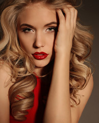 beautiful girl with blond curly hair and bright evening makeup, wears elegant dress